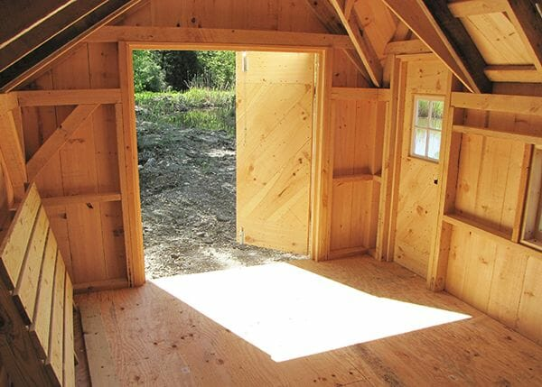 The 10x14 Dollhouse shed includes a set of double pine doors and a single door with a barn sash window installed in it.
