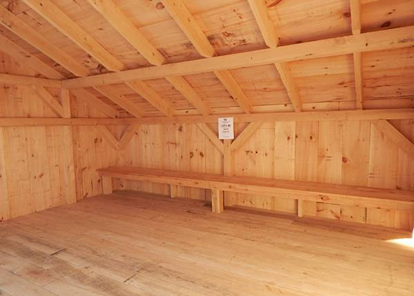 10x14 Camp Alcove with hemlock flooring and a pine bench.