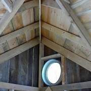 11x16 Bayside cabin interior with solid pine roof sheathing upgrade and insulated round window