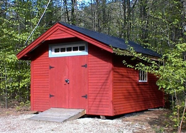 12x16 Gable - painted red shed with clapboard siding, black roof an custom windows. A roof overhang extension was also purchased on this fully assembled unit.