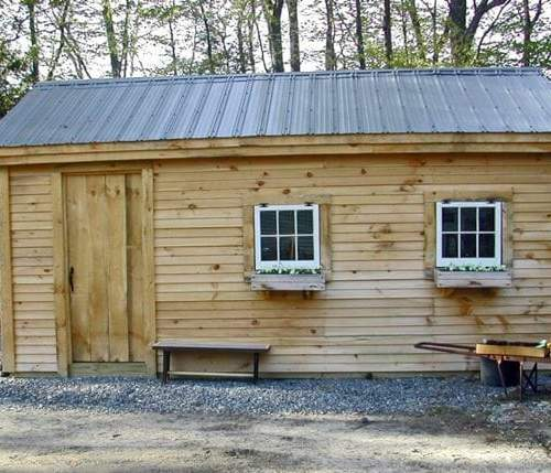 Post and Beam 12x20 Garage with gray metal roof, clapboard siding, hinged windows and flower boxes
