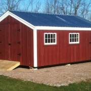 14x20 Barn that has been painted, with a matte black roof, windows and an extra door.