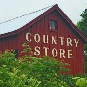 16x20 Barn that has been painted red with a wooden Country Store sign installed on it.