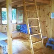 16x20 Vermont Cottage Option B includes a loft with ladder. This one has been finished out with interior sheathing