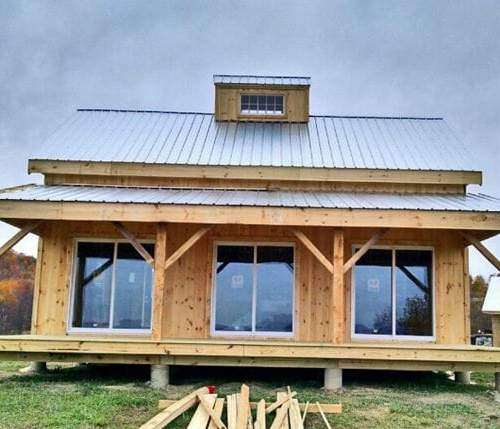 20x30 Vermont Cabin with 8x30 covered porch, custom cupola and client supplied sliding glass doors
