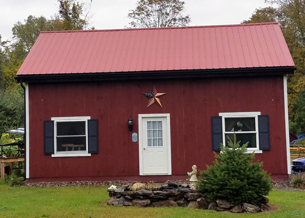 20x30 Vermont Cabin painted barn red with a red metal roof.