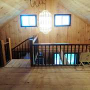 Custom built loft with railing in a 20x40 Vermont Cabin