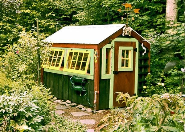 6x8 Greenhouse that has been painted green, yellow and brown with a custom door