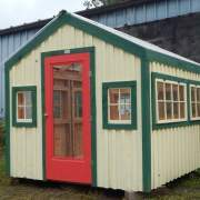 8x10 Greenhouse painted yellow with green trim and a red combo glass screen door
