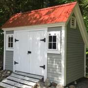 8x12 Saltbox storage shed customized with a red metal roof and clapboard siding