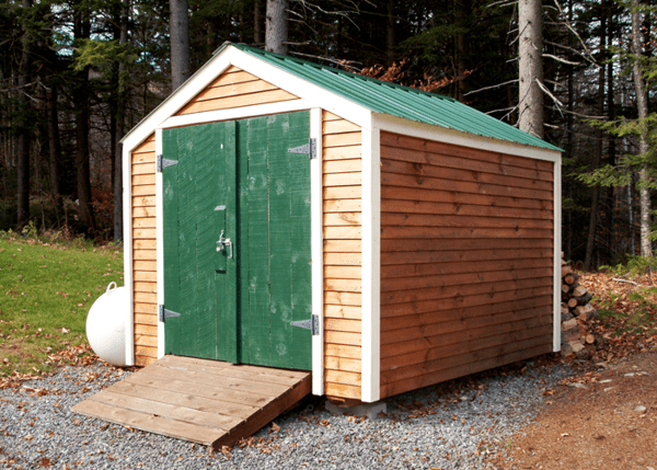 8x10 Vermonter with clapboard siding and a green door