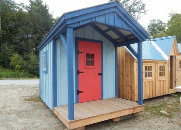 8x12 Nook post and beam cabin painted blue with a red door