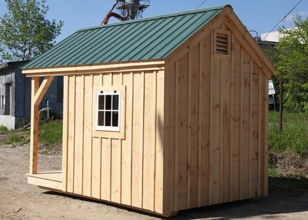 8x12 Nook post and beam cottage with pine board and batten siding and a green roof