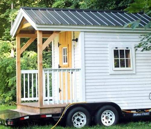 8x12 Nook tiny house painted white with clapboard siding, porch railing and a matte black roof installed on a trailer (client sourced)