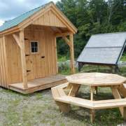 8x12 Nook post and beam cabin sitting next to an octagon picnic table and solar shed