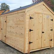This 8x12 New Yorker Option B garden shed was modified to have an extra door, clapboard siding and a black roof