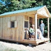 8x16 Bunkhouse with extra windows and screens. A couple with a dog are sitting on the porch