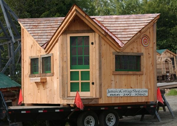 This small cottage is shown with a red cedar shingle roof, glass roundel, and a custom window and door layout with  aflower box.