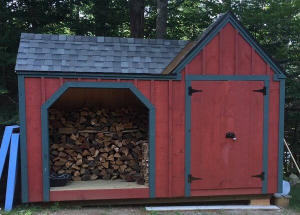 8x14 Vermont Gem firewood storage shed painted red with blue trim and an asphalt shingle roof
