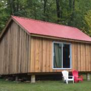 Custom built cottage with sliding glass door and red metal roof