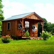 10x16 Pond House includes a green metal roof, pine board and batten siding and insulated windows and doors. This post and beam cabin includes a porch
