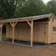 12x20 Three Sled Shed shown with an overhang and a couple hinged barn sash windows.