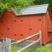 This Vermont Gem has been completely enclosed, painted red and has an extra set of double doors and a hinged barn sash window added. A flower box and charcoal gray roof are some of the other upgrades shown.