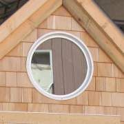 "The 24"" diameter insulated window adds a nice touch in the gable of a cabin."