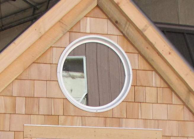"""The 24"""" diameter insulated window adds a nice touch in the gable of a cabin."""