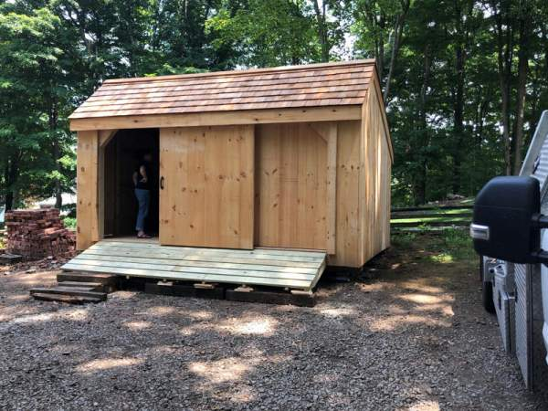 "5' JCS Built 2"" thick Pine Sliding Barn Door on 10x16 Three Sled Shed.  Exterior view."