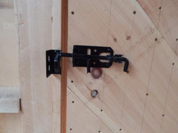 A black steel latch is included with the single pine door.