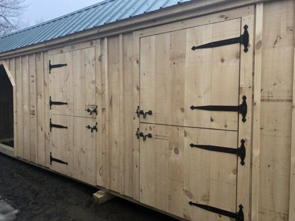 "4-0 JCS Built 2"" thick Pine Dutch Doors on 10x30 Three Stall Barn. Exterior view. Black Drop Latch & Strap Hinges."