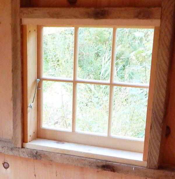 A hook latch secures the window when it is shut.
