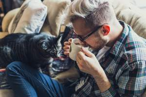 Alt tag: A man drinking coffee and a cat on his lap