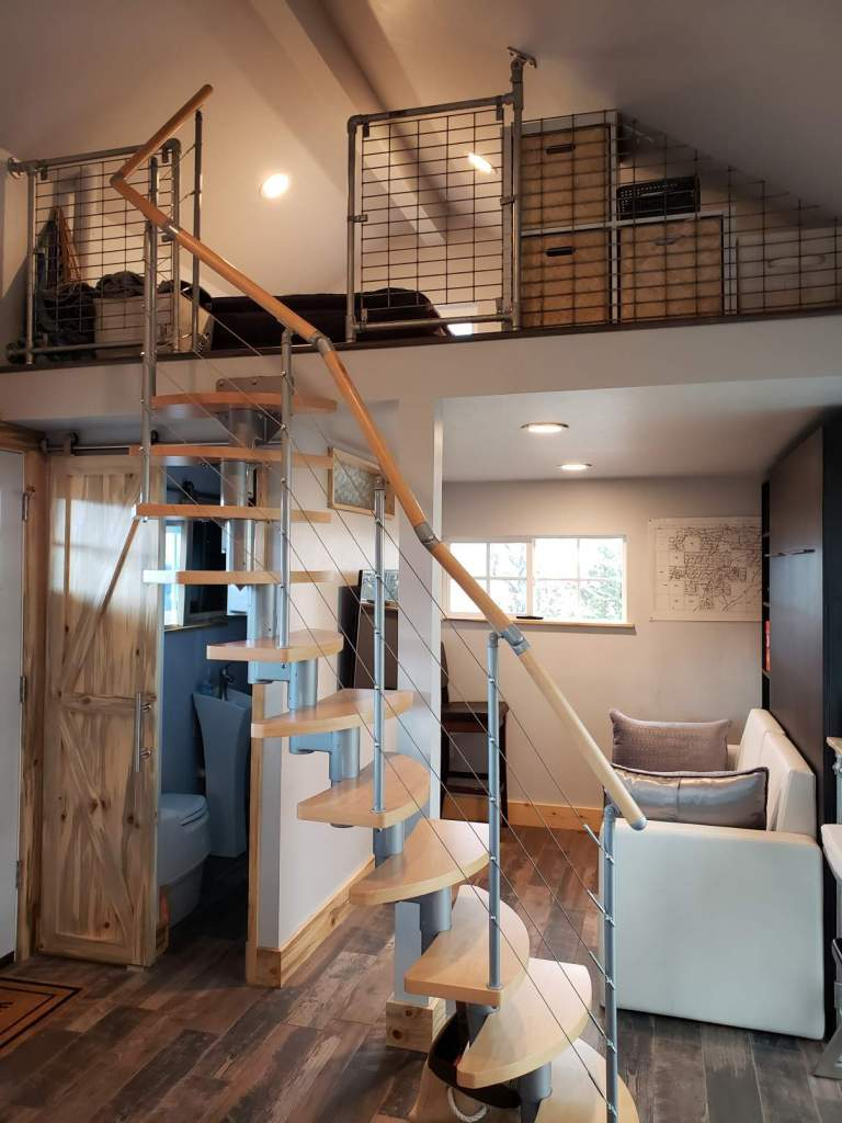 This beach house interior has a custom built staircase to the lof.t