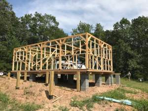 A post and beam timber frame being erected on top of a pier foundation.
